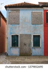 A blue, boarded up house on the island of Burano, Italy.  Burano is near Venice, and is famous for it's canals and colourful houses.