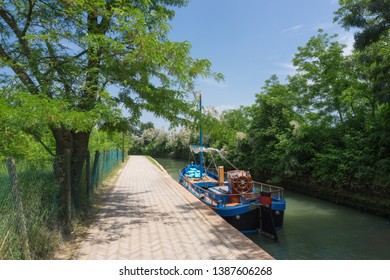 Blue boat in a canal next to the road to Santa Maria Assunta on Torcello, Venice / Italy, in bright sunny weather and blue sky