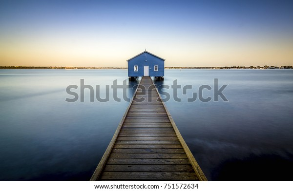 Blue boat house with a wooden pier leading to the front door. The Crawley Edge Boatshed (Blue Boat House) is a frequently photographed site in Crawley, Perth, Western Australia.