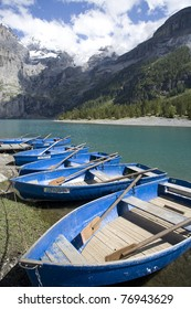 Blue boats at Oeschineensee in Switzerland.