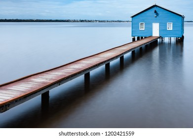 Blue boatshed at end of wooden jetty on wide expanse of blurred water