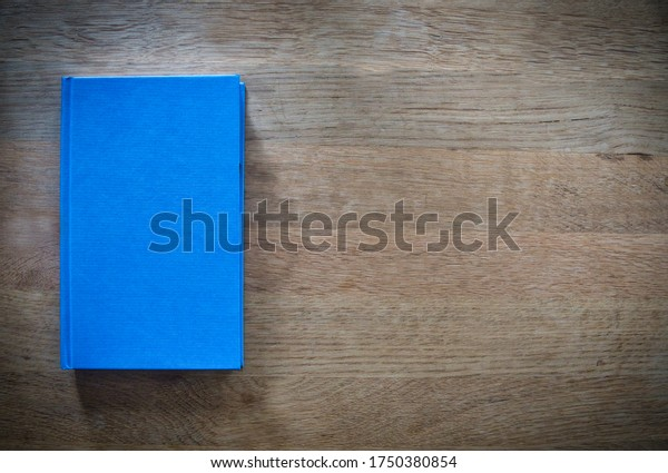 blue-book-on-wooden-table-600w-175038085