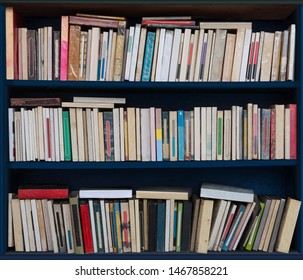 Blue bookshelf with many old books in various condition