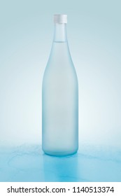 a blue bottle containing sake inside with reflection