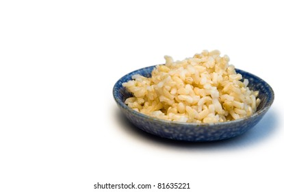 Blue bowl of brown rice on a white background.
