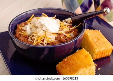 Blue bowl of elk meat chili sitting on plate with cornbread
