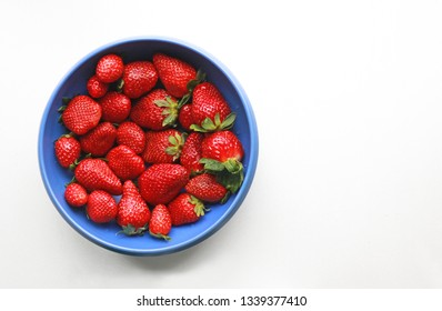 blue bowl filled with delicious fresh strawberries on white background, top view