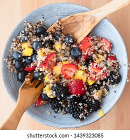 Blue bowl filled with fruit salad with quinoa,  strawberry slices, chopped nectarines. blackberries and blueberries on wooden surface, image 7 of 8