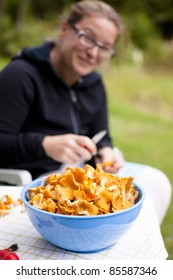 Blue bowl with fresh, picked chanterelles. Woman is rinsing the fungus in background