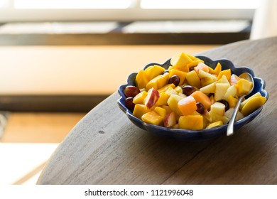 Blue bowl with fruitsalad of mango, apple, melon, grape and peach standing in the sunlight on a wooden table in front of a window in the kitchen
