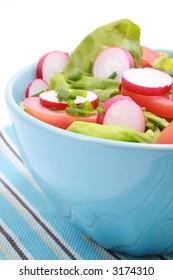 blue bowl full of fresh vegetables - salad - isolated on white
