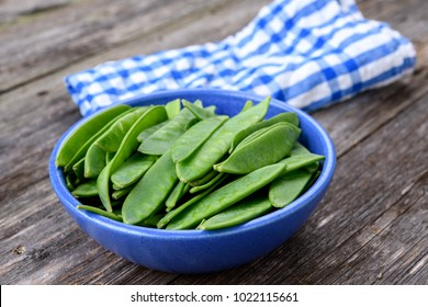 blue bowl with green peapods and towel