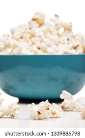 blue bowl with popcorn against white background