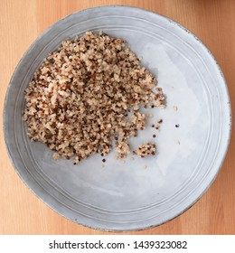 Blue bowl with quinoa on wooden surface, image 2 of 8
