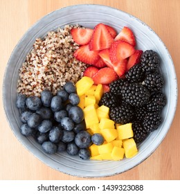 Blue bowl with quinoa,  strawberry slices, chopped nectarines. blackberries and blueberries on wooden surface, image 6 of 8