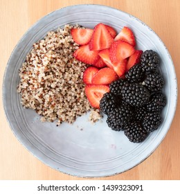Blue bowl with quinoa,  strawberry slices and blackberries on wooden surface, image 4 of 8