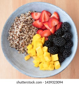 Blue bowl with quinoa,  strawberry slices, chopped nectarines and blackberries on wooden surface, image 5 of 8