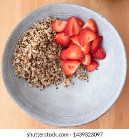 Blue bowl with quinoa and strawberry slices  on wooden surface, image 3 of 8