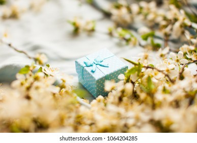 Blue box. Blue bogs with ring inside. Blue bow. White jasmine flower. branch of jasmine flowers. Tragic square funeral buttonhole from white jasmine flowers.