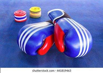 Blue boxing gloves with two rolls of hand bandage on blue exercise mat.