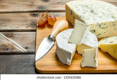 Blue and brie cheese on a chopping Board with a knife. On a wooden background.