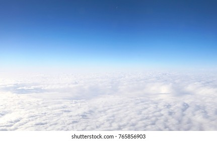 Blue bright clear sky above the clouds from the airplane window, aerial view. Beautiful texture of fluffy clouds. Airy light artistic image for dreams and travel.