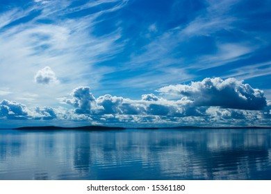 Blue bright summer sky with white clouds reflecting in lake. Srednee Kuyto Lake, Karelia, Russia