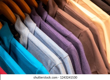 Blue brown shirts on hangs for sale in shop. Male textile on wooden hanger. Summer seasonal wear in department store. Unisex apparel for warm weather. Sale in shopping mall. Color gradient t-shirts