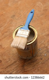 Blue brush on an opened can of varnish