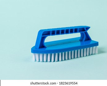 Blue brush with white bristles for cleaning on a blue background. The concept of cleanliness in the house.