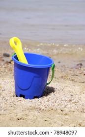 blue bucket with a shovel on seacoast
