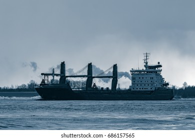 Blue bulk carrier sailing to the sea in cold winter. Monochrome