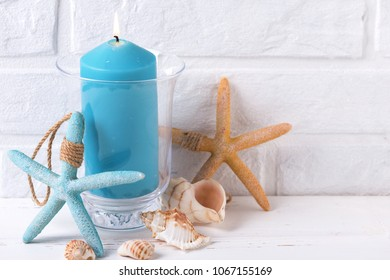 Blue burning candle, shells  and sea star  near by white brick wall. Selective focus. Place for text.