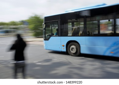 Blue bus driving by