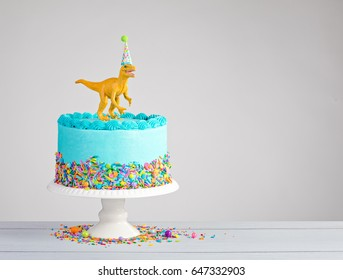 Blue buttercream birthday cake with toy dinosaur over a light grey background.