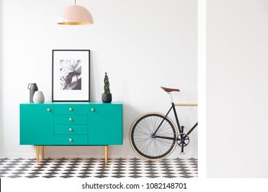 Blue cabinet with plant and poster in modern living room interior with bicycle and pink lamp