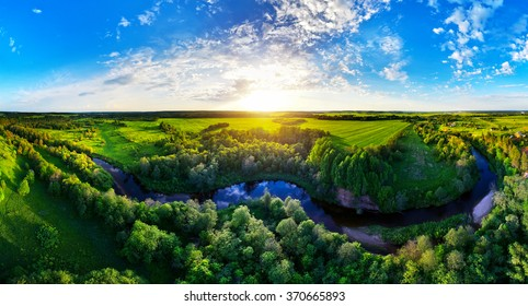 Blue calm river in the forest and fields at the sunset. Forest panorama aerial view from a drone.