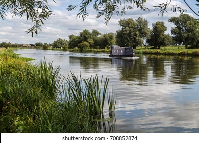 A blue canal boat approaches the cathedral city of Ely in Cambridgeshire on the River Great Ouse.
