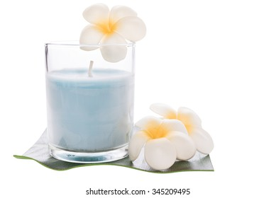 A blue candle in glass and frangipani flower isolated on white background with clipping path