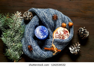 Blue candle and knitted scarf on wooden background. The concept of cozy Christmas decor.Hugge Style. Closeup.Copy space.