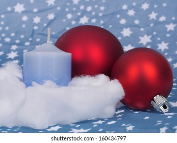 A blue candle with red Christmas ornaments decorated for Christmas