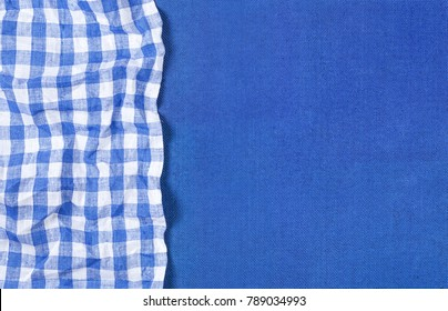 Blue canvas texture with blue checkered napkin for product presentation, top view