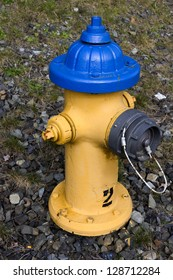 A blue cap yellow painted fire hydrant with rocky background