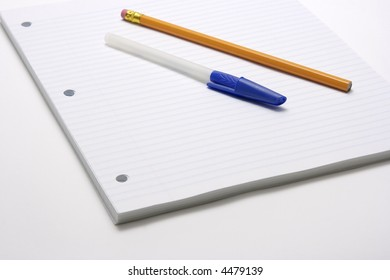 Blue capped pen and yellow pencil on blue lined and three hole punched paper for offices, businesses or back to school time.