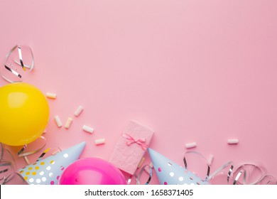 Blue caps, pink and yellow balls and silver serpentine on a pink paper background. Holiday background. Copy space, top view. - Shutterstock ID 1658371405
