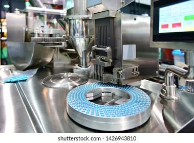 Blue capsule medicine pill production line, Industrial pharmaceutical concept.