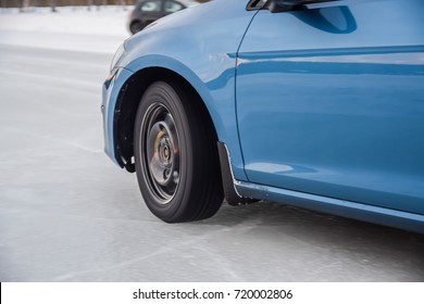 Blue car accelerates on absolutely frozen iced road surface. No asphalt, no tarmac under the wheel. Clean and clear ice under the wheel. Studded winter tires are in action.