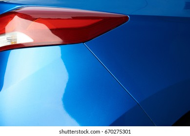 Blue car backlight  close-up. Shiny new polished blue car paint