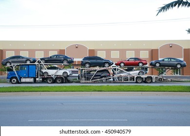 Blue Car Carrier Truck with Various Makes Models and Colors of Cars Parked on the Side of the Street with Green Grass and the Road Below and Brown Industrial Building Above in the Background