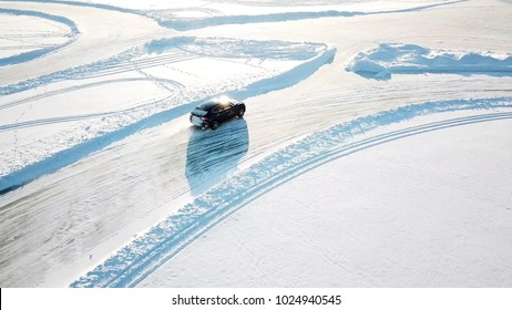 Blue car drives by icy track on snow covered lake at winter. Aerial view. Sport car racing on snow race track in winter. Driving a race car on a snowy road.